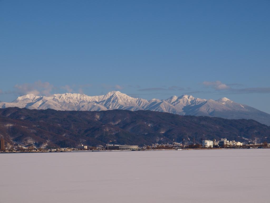 ほのかに色づく結氷した諏訪湖と八ヶ岳