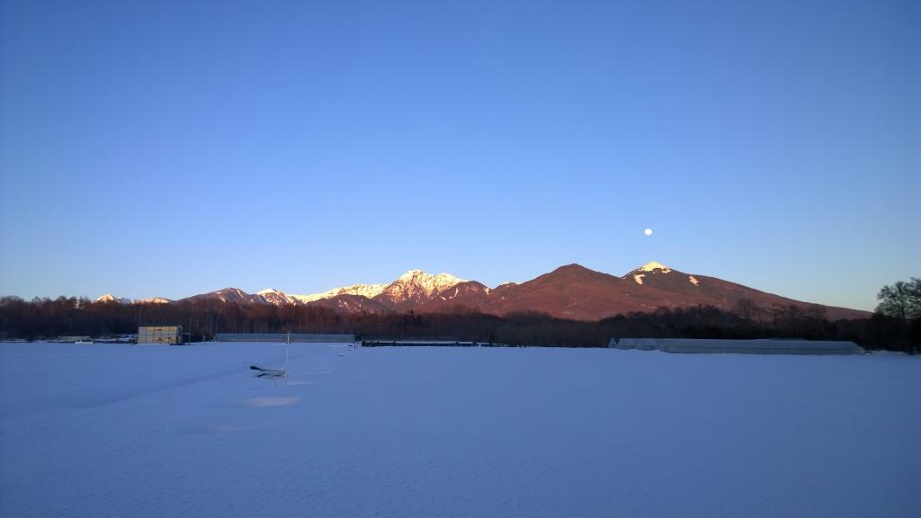 夕暮れの雪原と満月を頂く網笠山