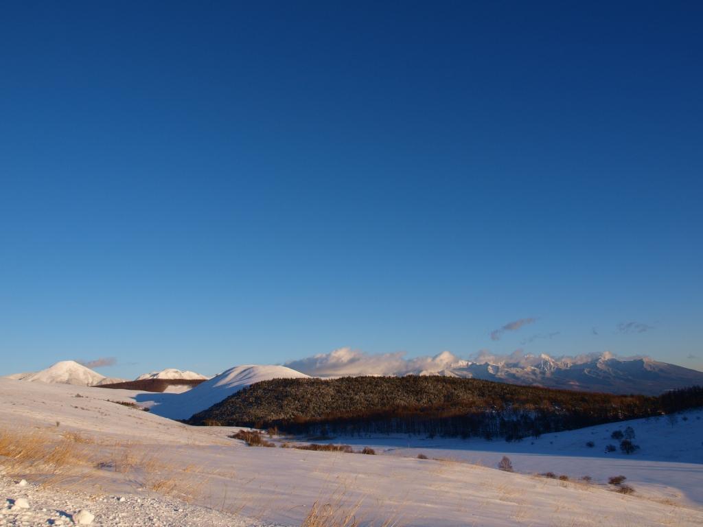 夕暮れの雪原となった池のくるみと八ヶ岳