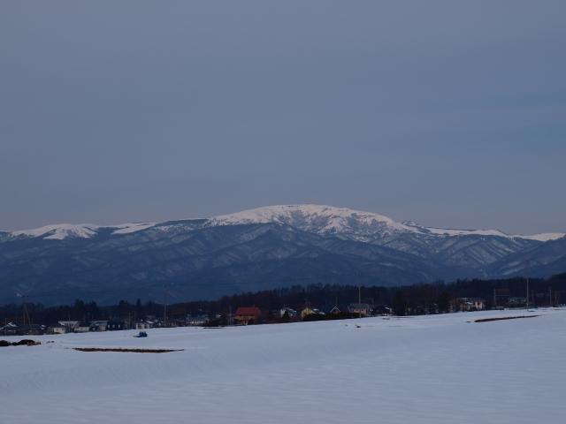 曇り空の雪原と車山