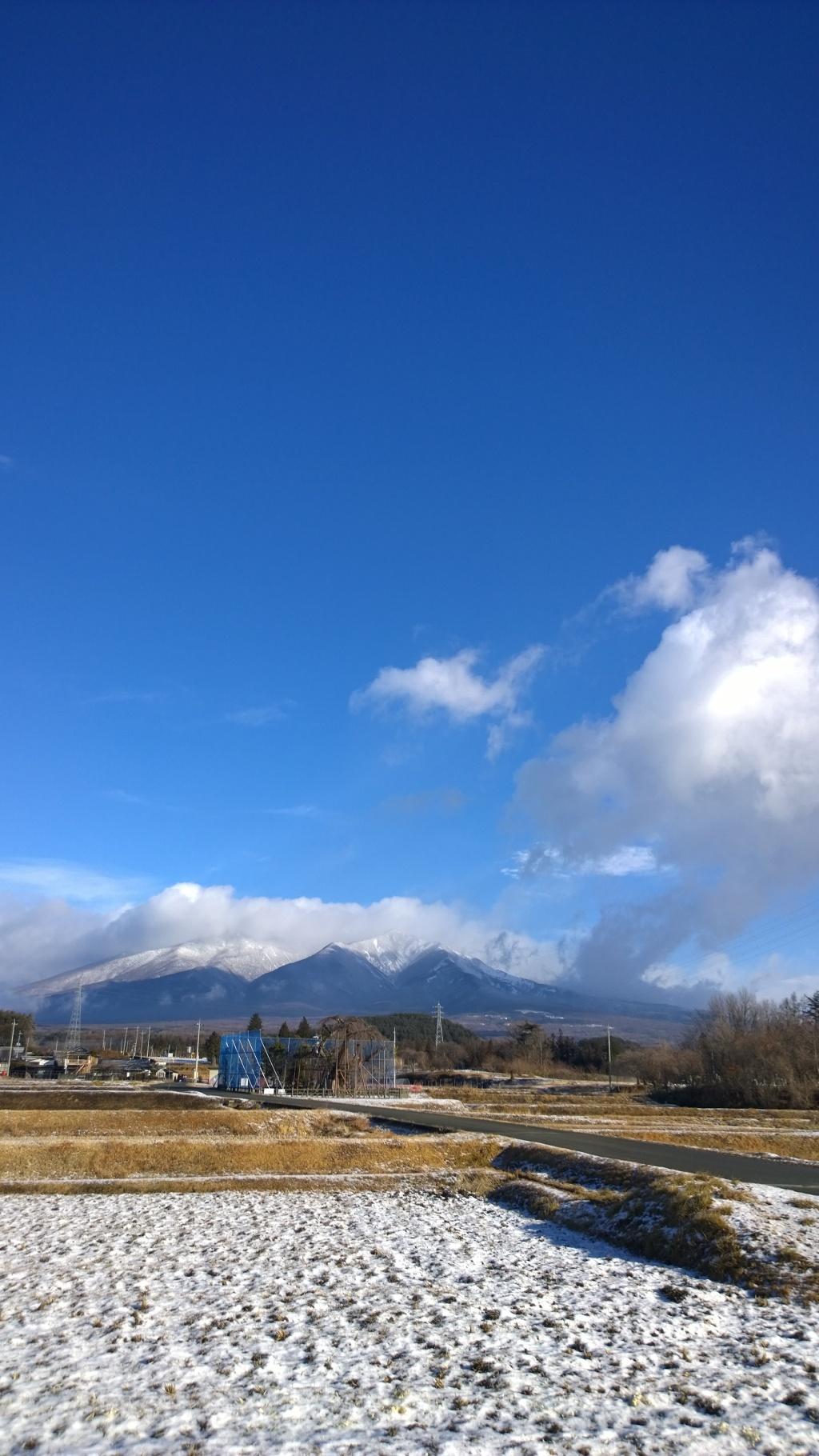 雪の八ヶ岳と雪が残る水田