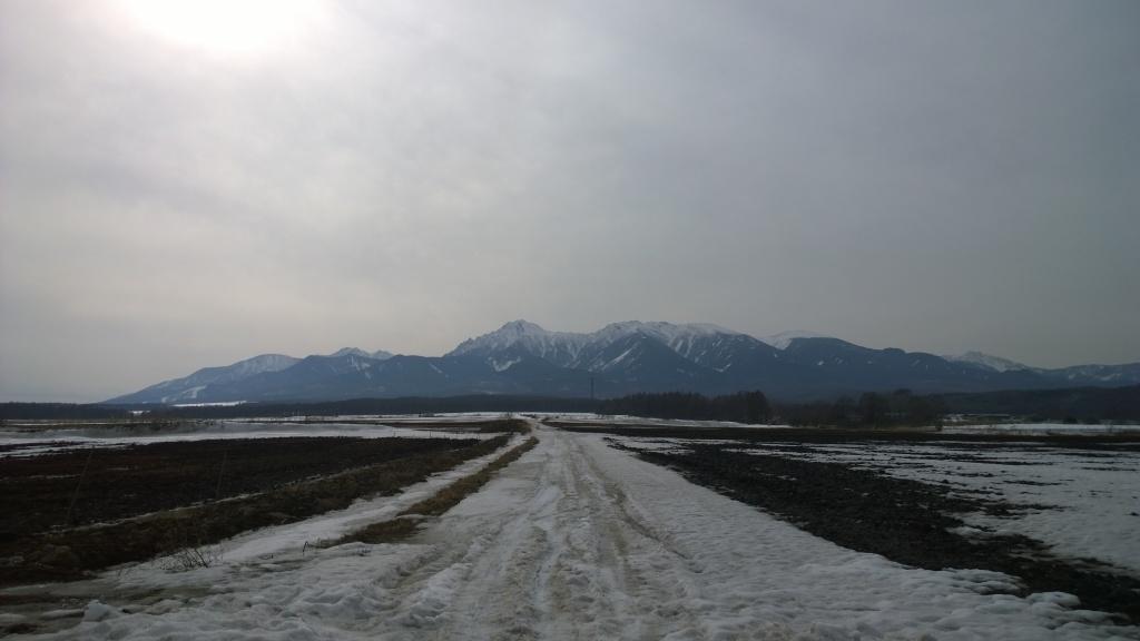 春先の雪原と八ヶ岳
