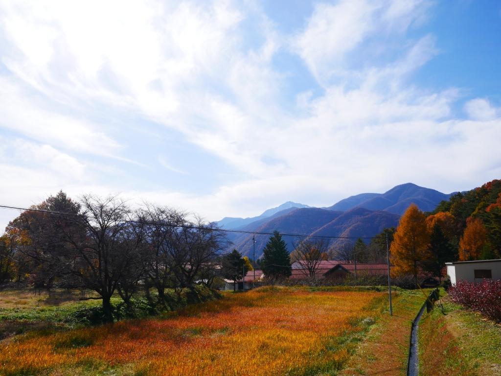 刈り取られた蕎麦畑と雲巻く南アルプス